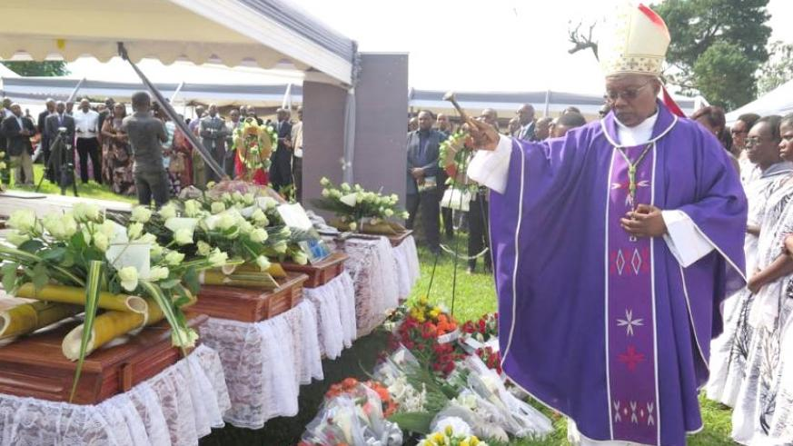 Bishop Philippe Rukamba of Butare Diocese sprinkles holy water on caskets containing the remains of some of the Genocide victims at the former ISAR Rubona in Huye District before t....