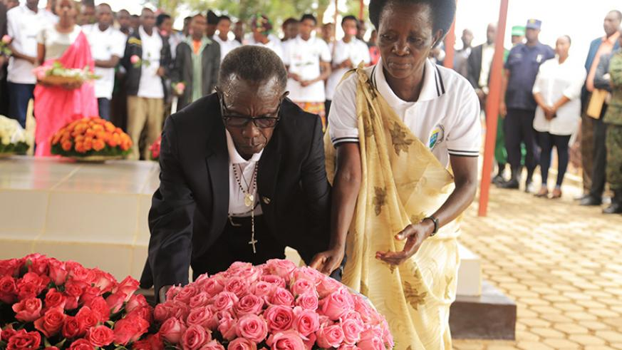 Parents of Imena Hero Marie Chantal Mujawamahoro lay a wreath on the grave of their daughter. Sam Ngendahimana.