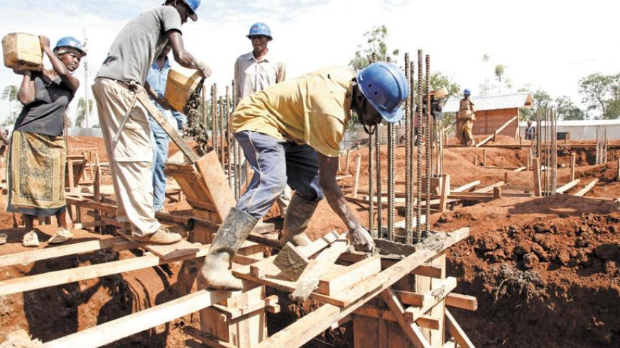 Builders at a construction site in Kigali last year. File.