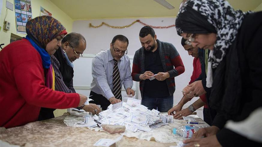 Staff members count ballots at a polling station in Cairo, Egypt.