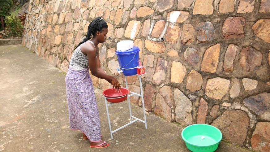 A lady washing her hands before stepping back home from a Boutique/Craish Bahizi